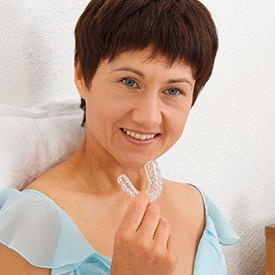 Smiling woman holding oral appliance