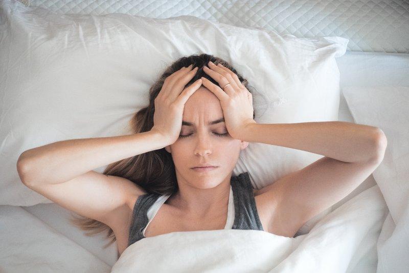 Woman with sleep apnea awake in bed with headache
