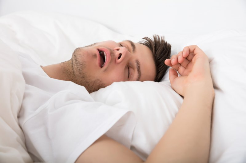 Young man lying on pillows and snoring