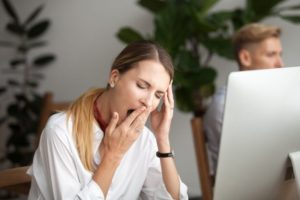 Woman with sleep apnea who looks tired at work