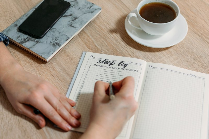 Writing in sleep log on a desk with cup of tea