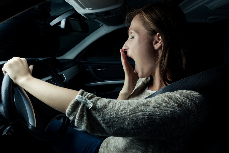 Woman yawning while holding steering wheel one-handed