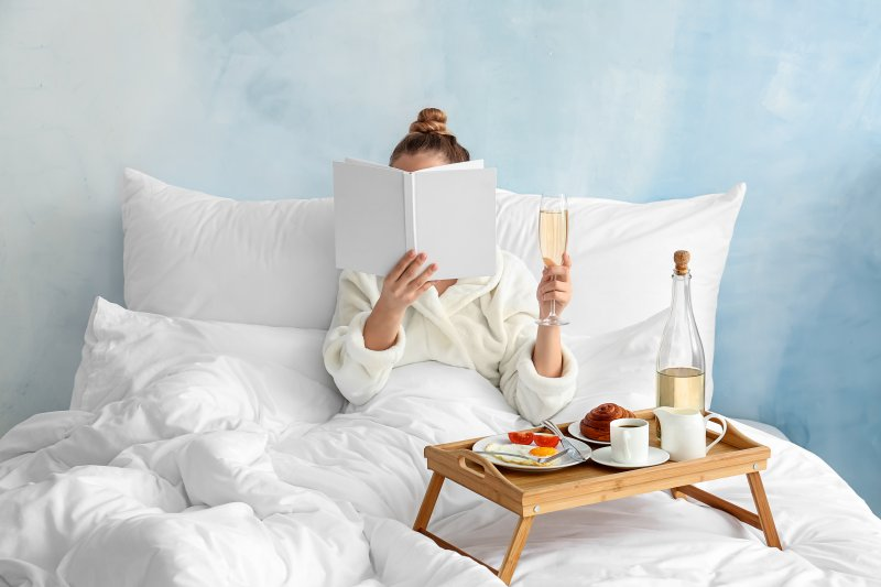 Woman having a glass of wine while reading in bed