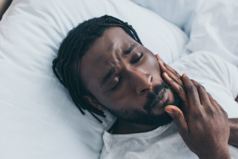 Man lying in bed feeling jaw due to TMJ pain