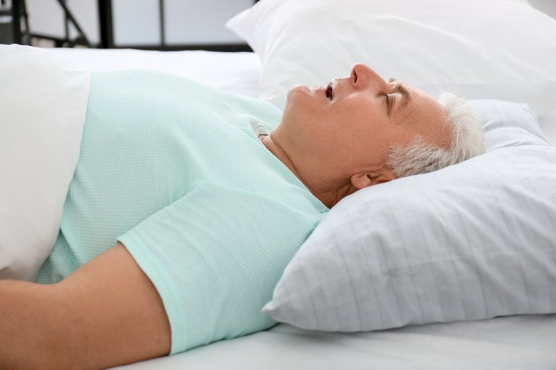 Man lying on back in bed mouth breathing