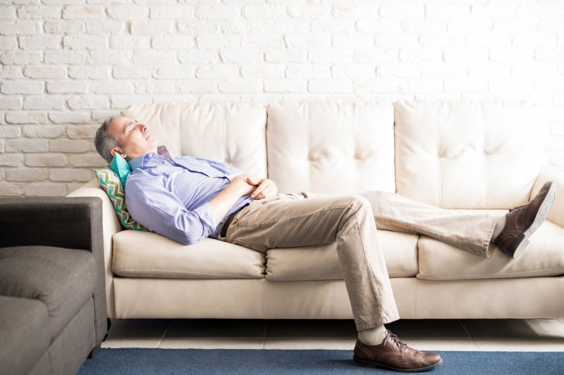 Middle aged man taking a nap on the couch