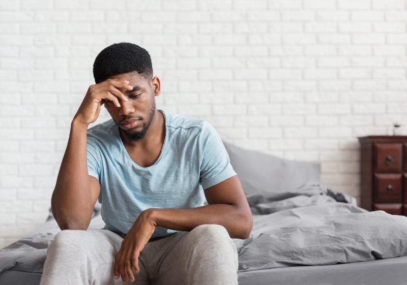 Man with sleep apnea and depression sitting on bed